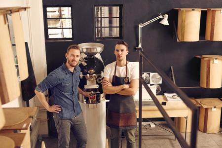 Portrait de deux hommes, le propriétaire et le gérant d'une société de torréfaction de café, en regardant avec confiance à la caméra dans leur espace de travail avec une nouvelle machine de torréfaction et des conteneurs de stockage modernes Banque d'images