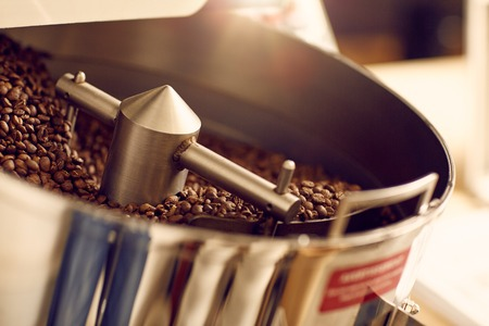 Aromatic coffee beans freshly roasted in a shiny and new modern appliance with clean metal parts in a roastery