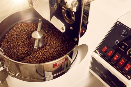 Modern appliance for roasting coffee beans looking shiny and new with a control panel with switches for various options of automated functions