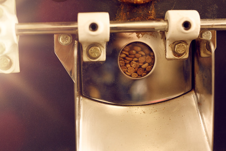 roasting: Closeup up detail of a modern appliance for roasting coffee beans showing a small window, through which one can view the raw beans ready for roasting inside the machine Stock Photo