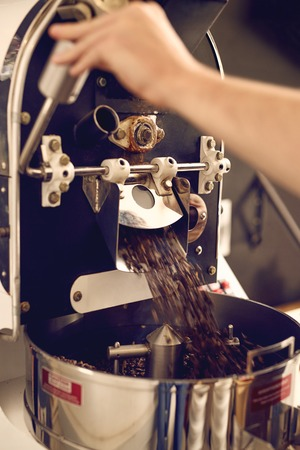 Cropped image of hands working a modern appliance that is dispensing the coffee beans it has freshly roasted into a shiny metal part below
