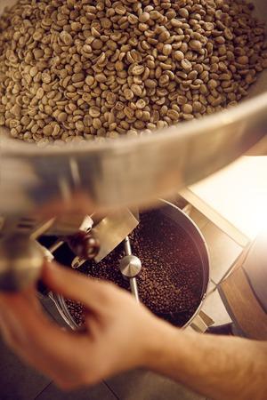 Overhead schot van de handen van een ervaren koffieboon koffiebrander, met behulp van een moderne glanzende apparaat met rauwe bonen zitten in het bovenste deel en vers gebrande bonen hieronder zichtbaar