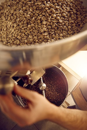 Overhead shot of the hands of a skilled coffee bean roaster, using a modern shiny appliance with raw beans sitting in the top part and freshly roasted beans visible below