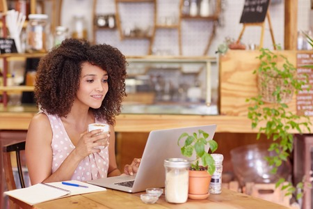 Beautiful young freelancer working on her laptop in a coffee with wifi Stock Photo