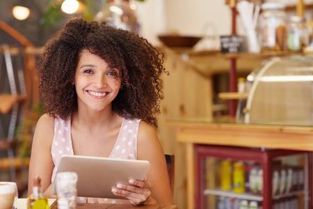 Mooie jonge gemengd ras vrouw lachend op de camera vol vertrouwen tijdens het gebruik van haar digitale tablet in een coffeeshop Stockfoto