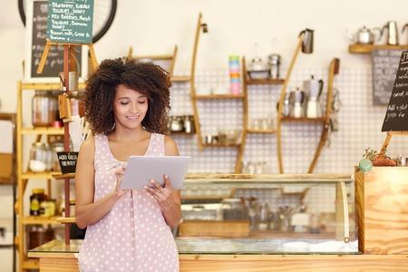美しいカフェのオーナーが彼女のコーヒー店のカウンターの近くに立っている間デジタル タブレットの助けを借りて彼女の中小企業を実行していま