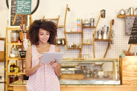 inside of: Beautiful cafe owner running her small business with the help of a digital tablet while standing near the counter of her coffee shop Stock Photo