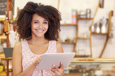 Portrait of a beautiful young woman with an afro hairstyle smiling at the camera while typing on her digital tablet in her coffee shop Stock Photo