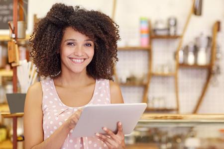 Portret van een mooie jonge vrouw met een afrokapsel die bij de camera glimlachen terwijl het typen op haar digitale tablet in haar koffiewinkel