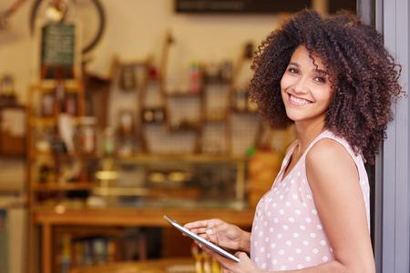 Mooi gemengd ras vrouw met een afro kapsel die een digitale tablet tijdens het staan in de deuropening van haar coffeeshop
