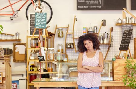 biznes: Młoda kobieta stojąca z ufnością w jej kawiarni, dumny z bycia właścicielem małej firmy Zdjęcie Seryjne