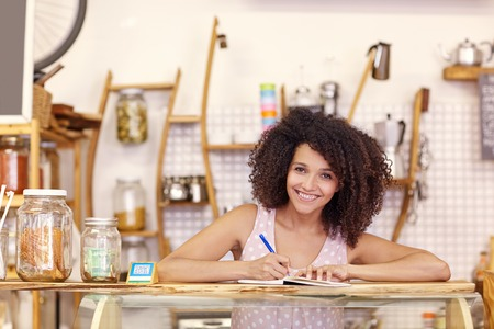 Beautiful young mixed race woman in her coffee shop writing out an order on the counter