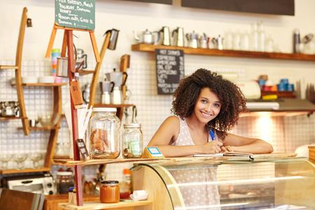 コーヒー ショップでのカウンターの後ろに立っている若い女性 写真素材