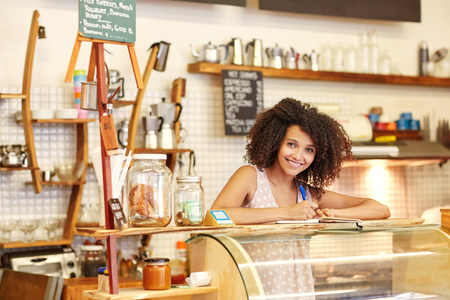 coffee shop: A young woman standing behind the counter in a coffee shop