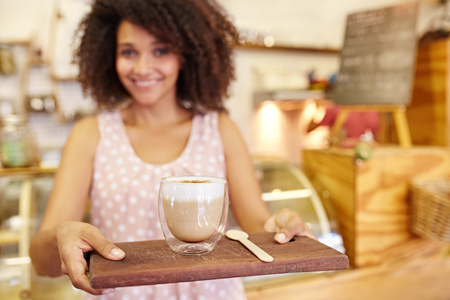 Focus on the foreground of a latte ay being carried on a wooden tray by a young mixed race waitress