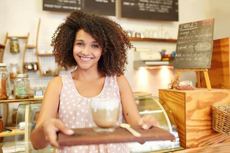 Una joven camarera que traiga una taza de café Foto de archivo - 51356873