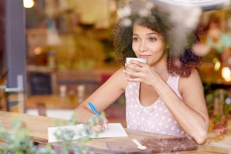 persona escribiendo: Hermosa mujer de raza mixta sentado en una cafetería sorbiendo su café con leche y soñando despierto mientras miraba por la ventana