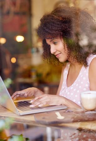 Mooie jonge vrouw met een afro kapsel werken op haar laptop in een coffeeshop Stockfoto