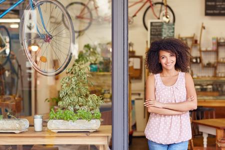 A mulher da raça misturada nova sorrindo, em pé na porta do seu café com os braços cruzados orgulho de ser o proprietário de um pequeno negócio