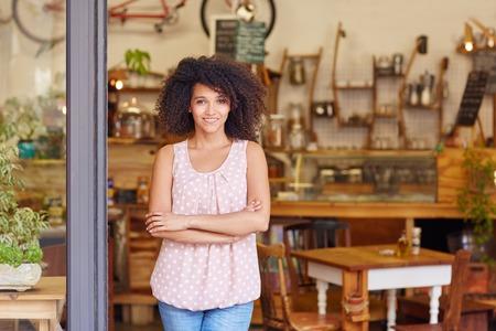 Hermosa joven dueño del café orgullosa de su pequeña sonrisa en la puerta de su tienda de café de pie de negocios Foto de archivo