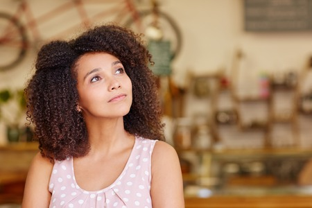mixed race woman: Mixed race woman in a coffee shop looking away thoughtfully and daydreaming