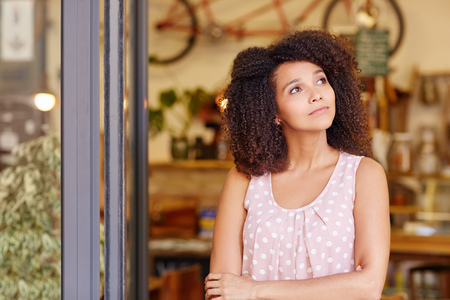 entrepeneur: Beautiful young woman standing in the doorway of her coffee shop thinking about the future of her small business Stock Photo