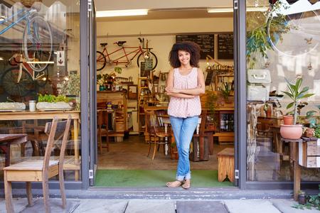 Volledige lengte shot van een jonge gemengd ras vrouw die gelukkig stond in de deuropening van haar trendy koffiebar Stockfoto