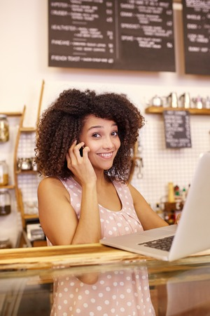 Young mixed race woman smiling at the camera while working on her laptop and taking a call on her phone Stock Photo