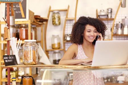 Happy young coffee shop owner talking on he mobile phone while typing on her laptop on the counter Stockfoto