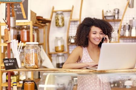 Propietario feliz joven tienda de café, hablando por teléfono móvil mientras se escribe en su computadora portátil en el mostrador