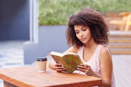 Young mixed race woman sitting a table outdoors with her takeaway coffee reading a book Stock Photo