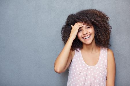 Een jonge vrouw lachend tegen een grijze achtergrond Stockfoto