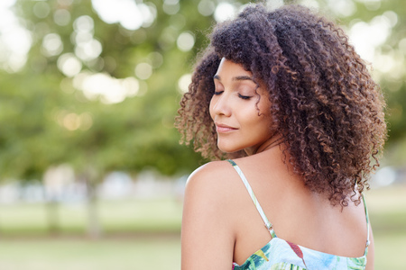Beautiful woman with curly hair looking relaxed with her eyes closed in a natural setting Banco de Imagens