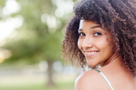 warmly: Closeup portrait of a beautiful mixed race woman smiling warmly over shoulder in a natural setting