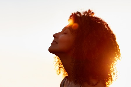 Profile protrait of a beautiful woman with afro style hair silhouetted against golden sun flare on a summer evening Foto de archivo