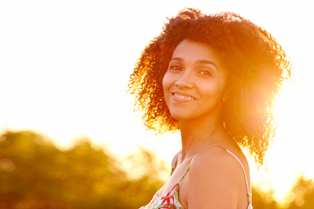 woman sunset: Closeup of a beautiful young woman with a sunset behind her