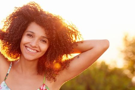 persona feliz: Primer plano de una mujer joven hermosa con una puesta de sol detr�s de ella