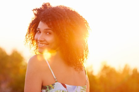 Beautiful mixed race woman looking back over her shoulder happily smiling at the camera with goldern sun flare Banque d'images