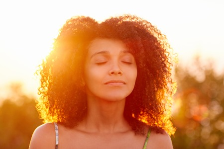 Beautiful woman with curly afro hair looking relaxed and happy with her eyes closed against a golden sunset with sun flare Stock Photo