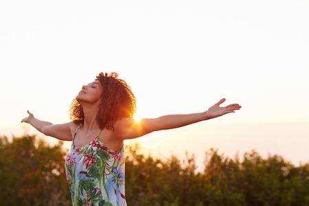 Mooi gemengd ras vrouw uiting vrijheid buiten met haar armen uitgestrekt Stockfoto