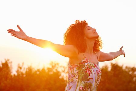 Mooi gemengd ras vrouw uiting van vrijheid op een zomerse avond buiten met haar armen uitgestrekt