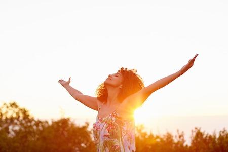 Een mooie jonge vrouw met uitgestrekte armen bij zonsondergang