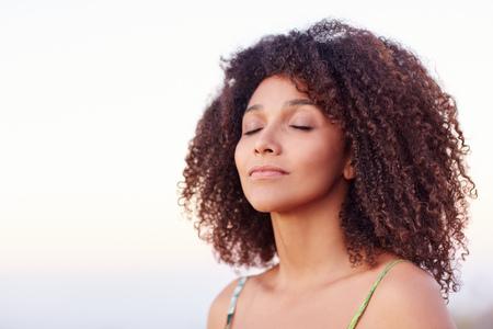 彼女の目を持つ美しい混血女性は穏やかな瞬間に屋外閉鎖