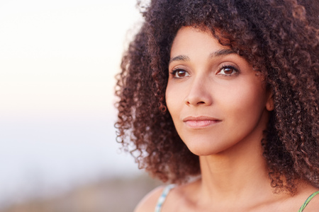 Intimate closeup portrait of a beautiful mixed race woman outdoors looking serenely into the distance photo