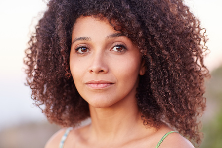hispanic woman: Closeup and intimate portrait of a beautiful mixed race woman looking at the camera outdoors Stock Photo