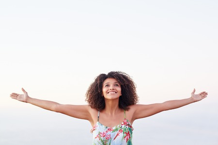Happy mixed race woman with outstretched arms outdoors expressing freedom photo