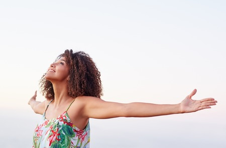 Beautiful mixed race woman expressing freedom with her arms outstretched outdoors photo