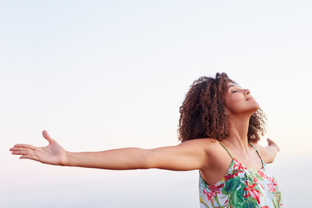 Femme en plein air avec ses bras tendus et les yeux fermés exprimant la liberté sereine