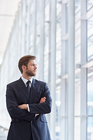 confidently: Corporate executive in a modern architectural setting looking confidently out of high rise windows