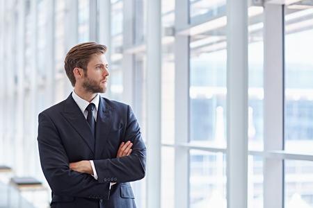 Corporate executive in een moderne architectonische omgeving kijkt vol vertrouwen uit hoogbouw ramen Stockfoto